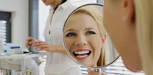 Dental-patient-smiling-in-mirror-horizontal